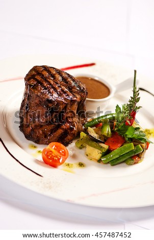 Steak with vegetables garnish  and sauce demi glace Isolated on white - stock photo