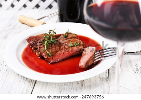 Steak with wine sauce on plate with bottle of wine on wooden background - stock photo