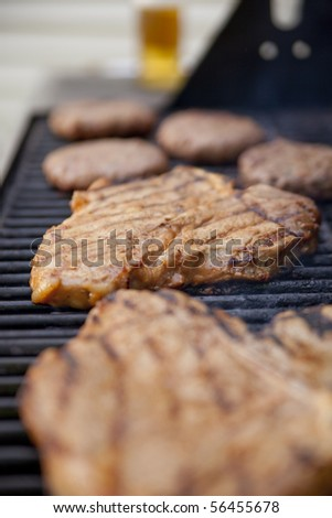 Steaks and burgers on the grill with a bottle of beer out of focus on the background. Shallow DOF on the second steak. - stock photo