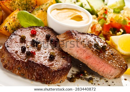 Steaks, baked potatoes and vegetable salad  - stock photo