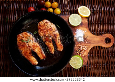 Steaks of red fish grilled for two people, is a pan on a wooden board close tomatoes and slices of lemon and lime - stock photo
