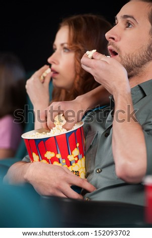 Stealing popcorn. Young men stealing popcorn during the movie session at cinema - stock photo