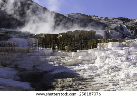 Steam and hot water being released from a geothermal hot spot in Yellowstone National Park, Wyoming, United States  - stock photo