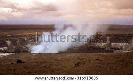 Steam and smoke rising from the active Halemaumau crater in Volcanoes National Park on the Big Island of Hawaii - stock photo