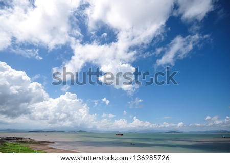 steam boat sailing on the sea near coastline with beautiful cloudscape in the sky - stock photo