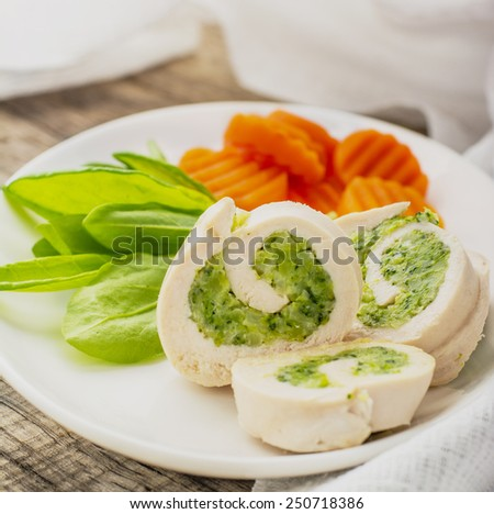 Steam dietary roll chicken breast stuffed with broccoli. Sliced portions on a white plate with sauce and fresh vegetables. Concept of healthy food. Selective focus. top view. - stock photo