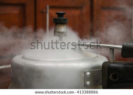 Steam escaping from lid of pressure cooker with reflection of modern kitchen. Indian style cooking rice or dhal  - stock photo