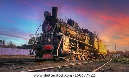 Steam locomotive at sunset. - stock photo