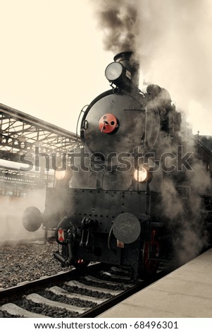 Steam locomotive at the railway station wrapped up in cloud - vintage retro tinting - stock photo