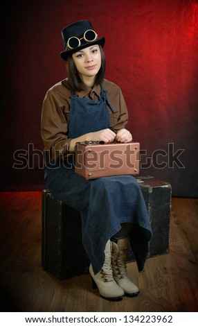 Steam punk girl sitting on suitcase. Looking at camera. - stock photo
