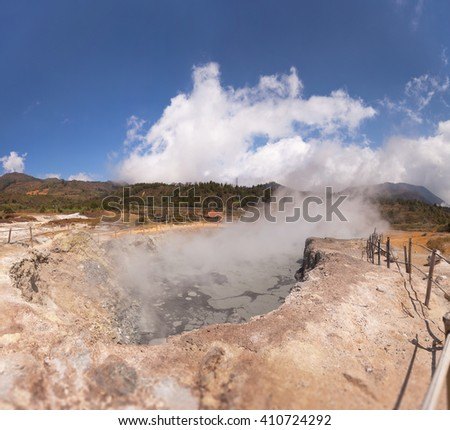 Steam rises from a natural, geothermal heated geyser in Java, Indonesia, under a deep, blue sky.