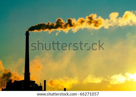 Steam rises from a smokestack on a factory silhouetted against the sunlight. - stock photo
