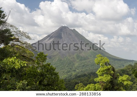 Steam rises from Arenal volcano in Cost Rica is framed by the beautiful tropical rain forest of La Fortuna.  Arenal is one of seven major volcanos in the country.  - stock photo