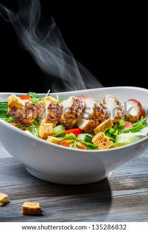 Steam rising from a freshly chicken Caesar salad - stock photo