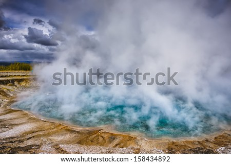 Steam rising from the turquoise waters of Excelsior Geyser Crater in Midway Geyser Basin, Yellowstone National Park, Wyoming - stock photo