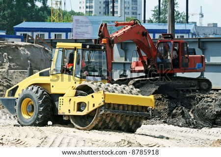 Steam roller and excavator. - stock photo