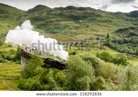 Steam train on Glenfinnan Viaduct / The famous Glenfinnan Viaduct which carries the steam train from Fort William to Mallaig - stock photo