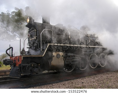 Steam train standing at the ashes pits warming up and being cleaned before taking off on a trip - stock photo