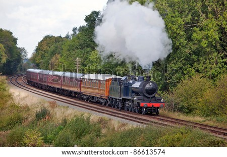 Steam train taking passengers on a short excursion through country woodlands - stock photo