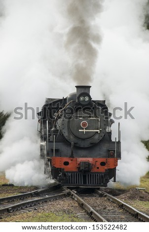 Steam train traveling along the railway line with steam bellowing out the sides and the top