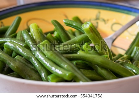 Steamed beans with oil in home style bowl. Angle close up. Fork in bowl, blurred in background. Tasty home made meal from garden vegetables.
