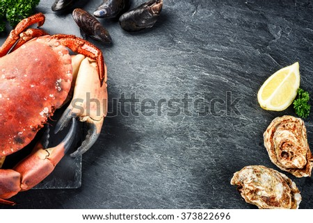 Steamed crab and fresh oysters on dark background. Sea food dinner concept  - stock photo