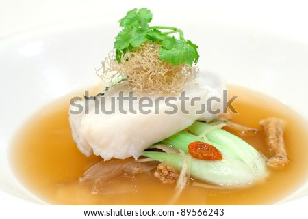 Steamed fillet of cod on a bed of vegetables in wolf berry sauce, topped with shredded fried ginger and  Chinese parsley