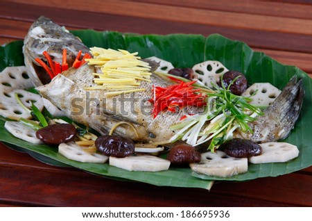 steamed grouper with soy sauce mushroom, ginger and vegetable , a typical Vietnamese cuisine so called  CA MU HAP XI DAU. - stock photo