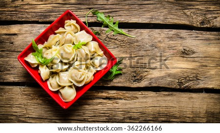 Steamed homemade ravioli with herbs in a Cup. On wooden background. Free space for text . Top view - stock photo