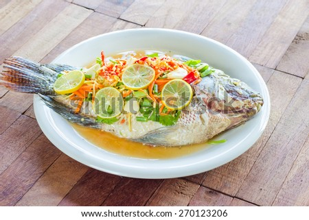 steamed Nilotica fish,thai style steamed fish in spicy sauce,wood background - stock photo