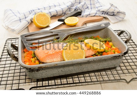 steamed salmon fillet on finely chopped vegetable in a serving tray - stock photo