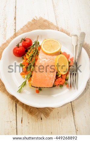 steamed salmon fillet on finely chopped vegetable, tomato and lemon on a plate - stock photo