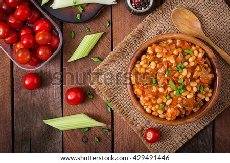 Steamed white beans with meat in tomato sauce. Top view - stock photo