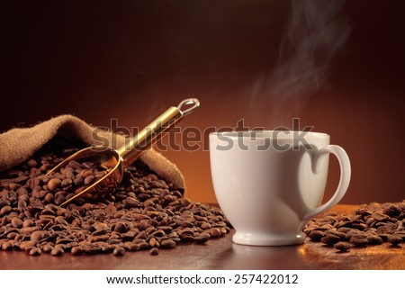 Steaming coffee cup with heart shaped handle shadow, coffee scoop and a heap of coffee beans - stock photo