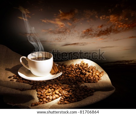 Steaming cup of coffee, cinnamon sticks and a few coffee beans. still life