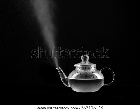 steaming glass teapot on black background - stock photo