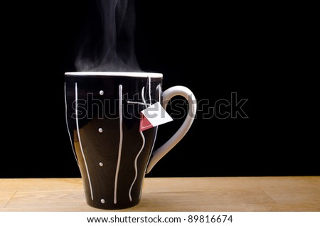 Steaming hot cup of tea on a table with black background - stock photo