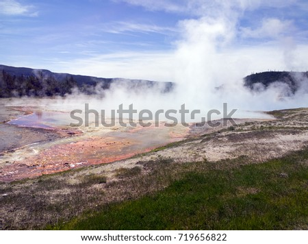 Steaming hot spring at Yellowstone National Park, sulfurous vapor rising, the water heavy with minerals.