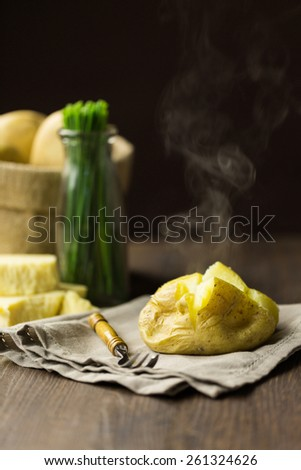 Steaming jacket baked potato with chives and cheddar cheese - stock photo