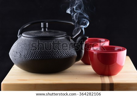 Steaming Teapot and cups - stock photo
