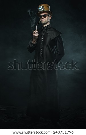 Steampunk man in a long coat smoking a pipe - stock photo