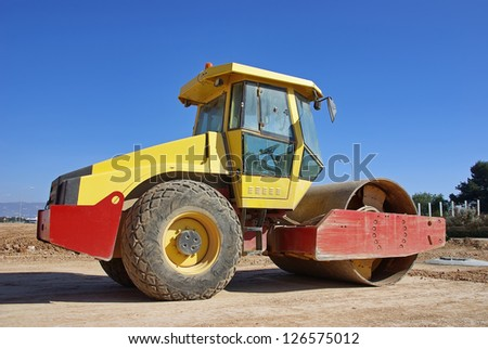Steamroller in a construction site - stock photo