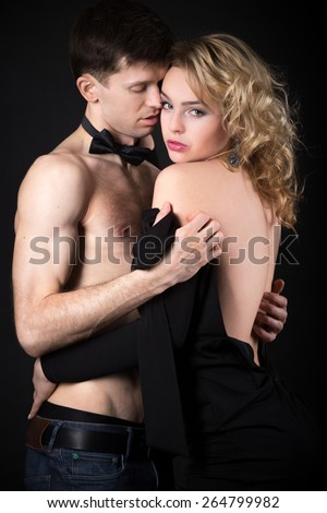 Steamy scene after party, beautiful young couple caught up in the middle of undressing before sex, woman in evening dress looking at camera, studio, black background