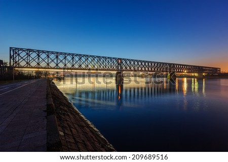 Steel bridge across river at night