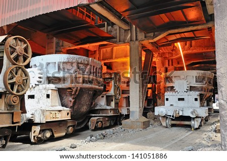 steel buckets to transport the molten metal inside of plant - stock photo