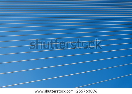 Steel cables over sky background. Abstract pattern. - stock photo
