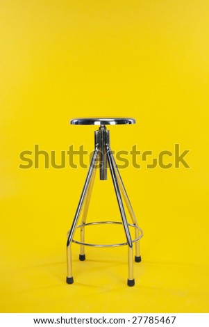 steel chair in yellow background - stock photo