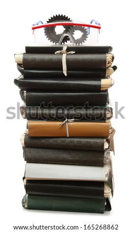 Steel cogwheels and goggles on stack of old paper folders - stock photo