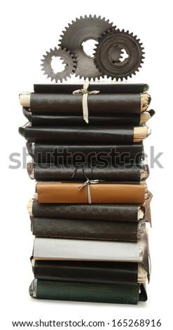 Steel cogwheels on stack of old paper folders - stock photo