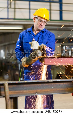 Steel construction worker cutting metal with an angle grinder - stock photo